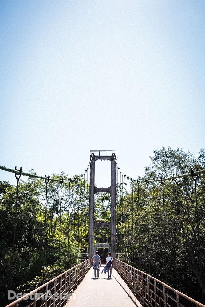 A pedestrian-only suspension bridge across the Luosuo River connects the Xishuangbanna Tropical Botanical Garden with Menglun Town.