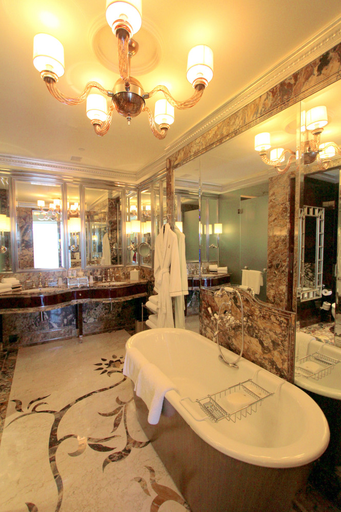The opulent bathroom has a tub that sits right opposite a television screen.