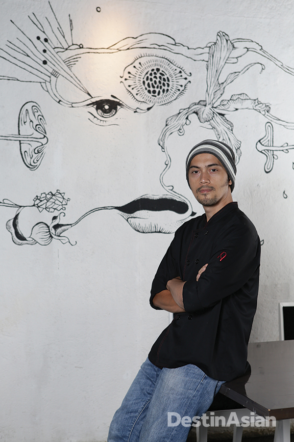 Chef Andrian Ishak in front of a mural of his own design on the restaurant's back wall.