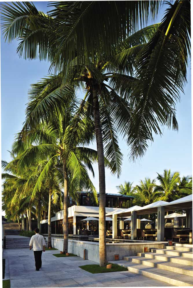 Palm trees flank the dining terrace at the Nam Hai's main restaurant. Opposite: High chairs meet high design in a corner of the InterContinental Danang Sun Peninsula Resort's exuberantly decorated Citron restaurant.