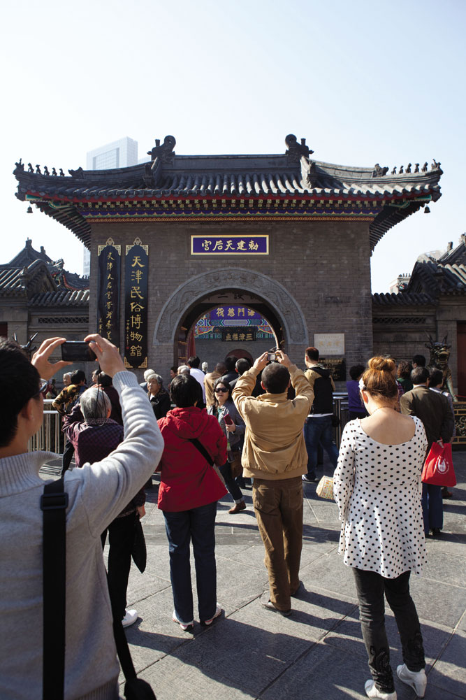 Snap-happy tourists on Tianjin's Ancient Cultural Street, an avenue lined with reproductions of Qing-era architecture.