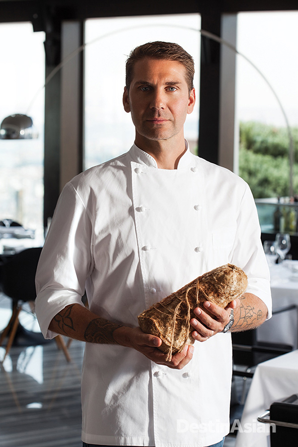 Chef Mehmet Gurs in the dining room at Mikla, with a block of Divle cave-aged cheese from Karaman province.
