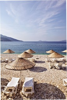 Woven-rush umbrellas shade sun loungers at Kalkan, an old Ottoman-Greek village that has emerged as the ideal base for exploring Turkey's Lycian coast.