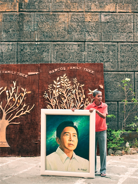 Catalino Bactat, caretaker of  the Marcos Museum and Mausoleum in Batac, with a portrait of the former Philippine president.