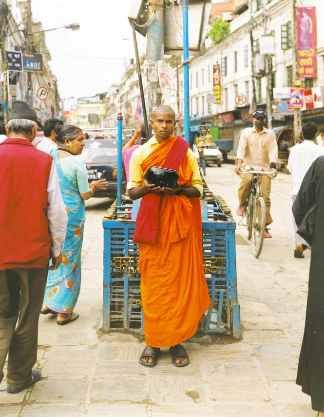 A Buddhist monk collecting alms at Indra Chowk.