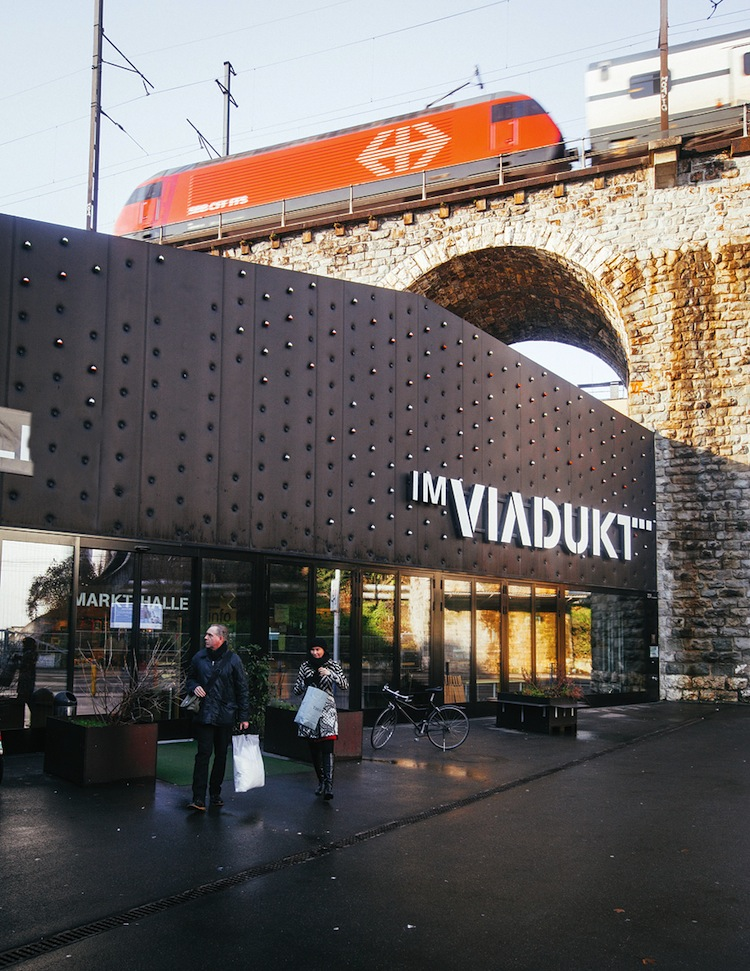 An S-Bahn commuter train passing over Im Viadukt, a stretch of renovated railways arches that now house shops and an indoor market.