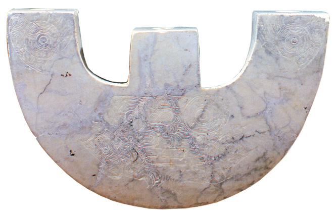 A white-jade huang pendant.