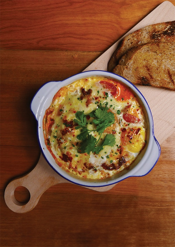 Frisky Goat's baked eggs with sausage, bacon, tomato, cream, and cheese.