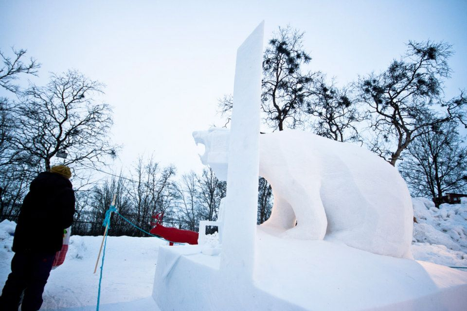 A visitor inspects a sculpture at the Kiruna Snow Festival. Photo by Martin Smedsen