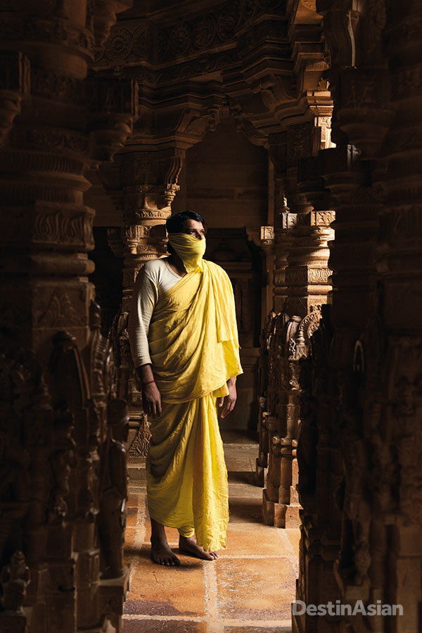 A Jain monk of the Shvetambara sect in the sanctum of Jaisalmer Fort's Parshvanath Temple. Shvetambara ascetics wear muslin cloths (muhapatti) over their mouths to avoid inadvertently killing insects by inhaling them.