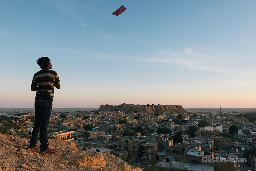 A hill outside town provides the perfect perch for a young kite flier - not to mention a stunning view over Jaisalmer and its centerpiece fort.
