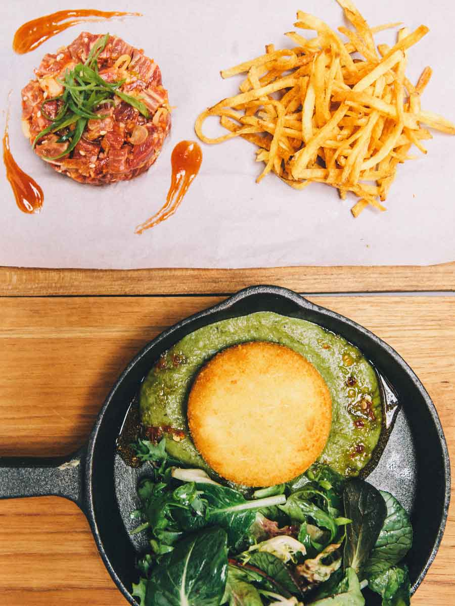 A blue swimmer crab cake with mesclun salad and beef tartare with fries at Potato Head Garage.