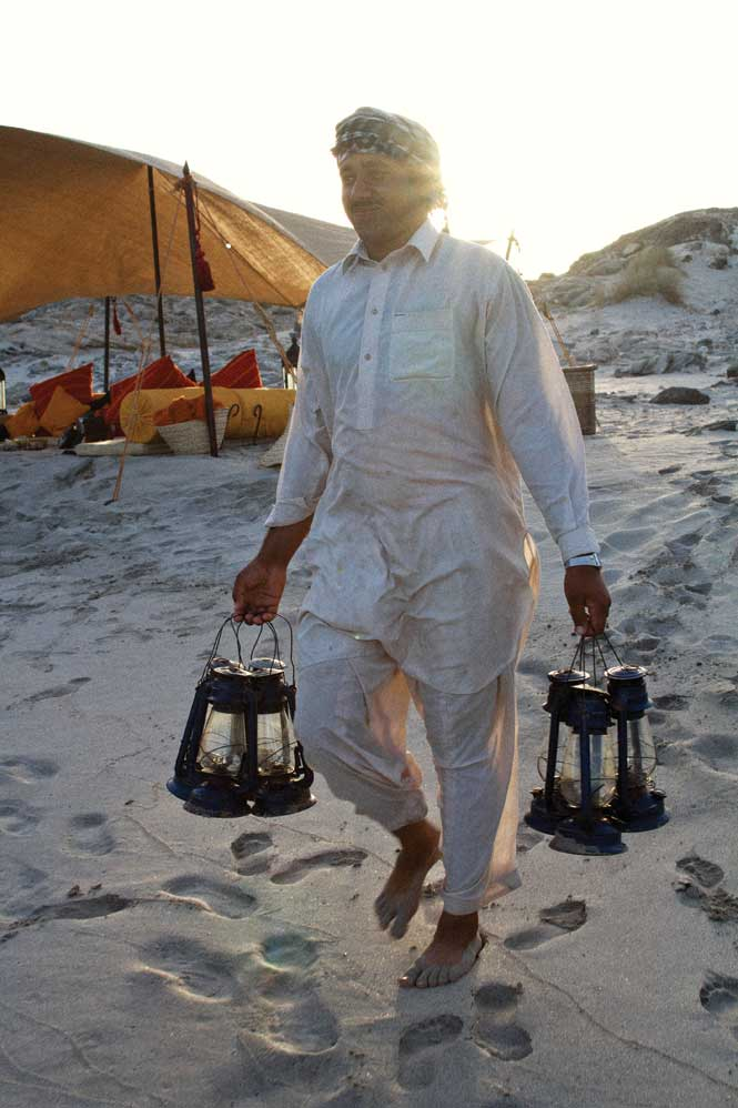 Setting up lanterns at the beach camp near Mirbat.