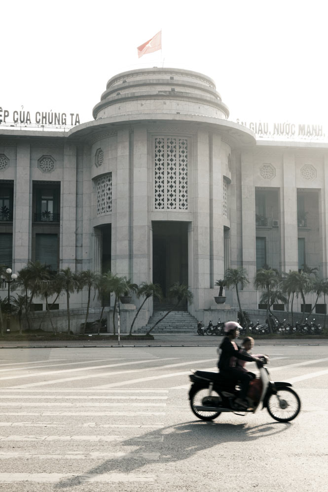 Motoring past the Art Deco–style State Bank of Vietnam.