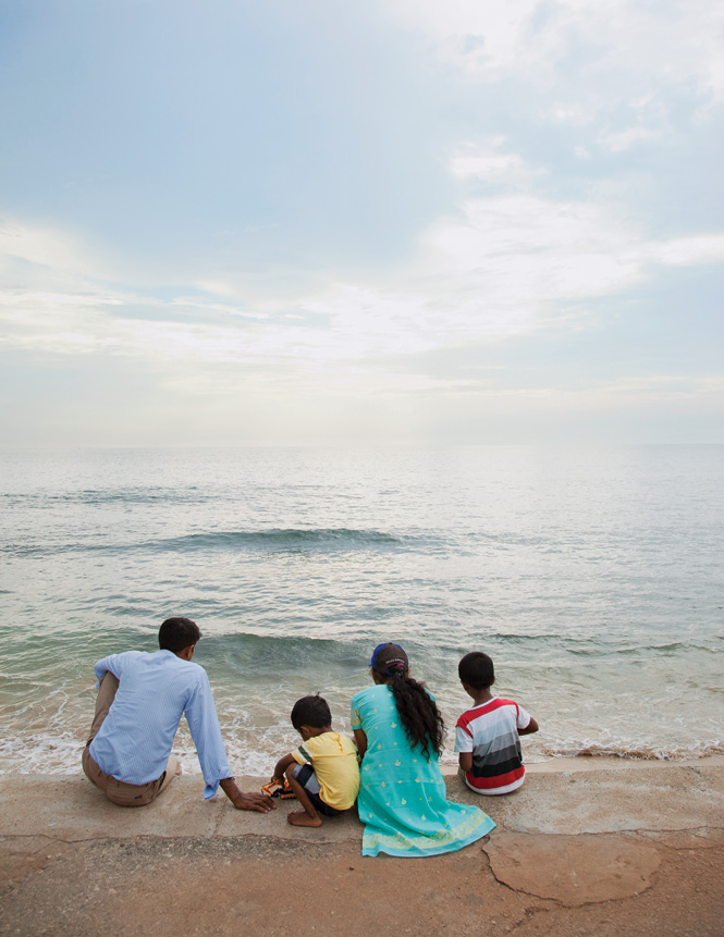 A Sri Lankan family watching the tide come in at Galle Face Green, Colombo's historic seaside promenade.