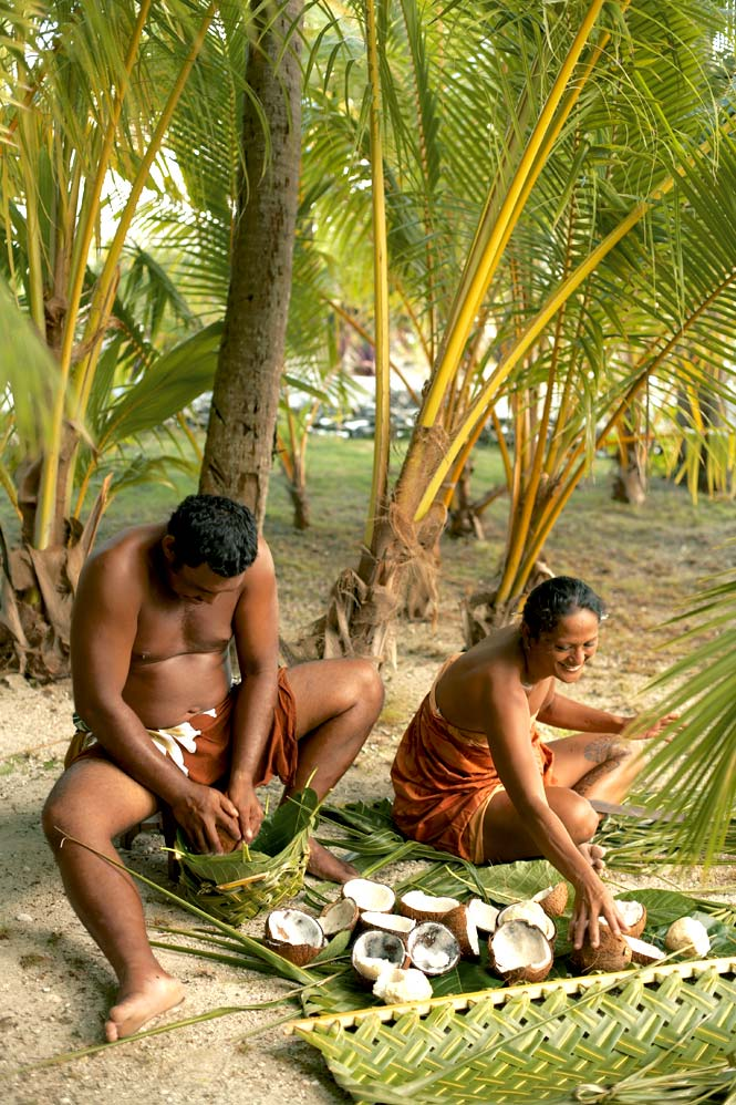 Islanders grinding ripe coconuts on the atoll of Tikehau
