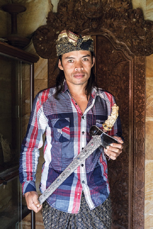 Made Pada holds one of his creations, a silver-sheathed kris with a gold handle.