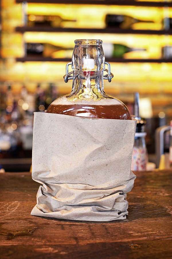 The Black Stripe at Mama San, served in a glass flask covered by brown paper bag as a throwback to the Prohibition era.