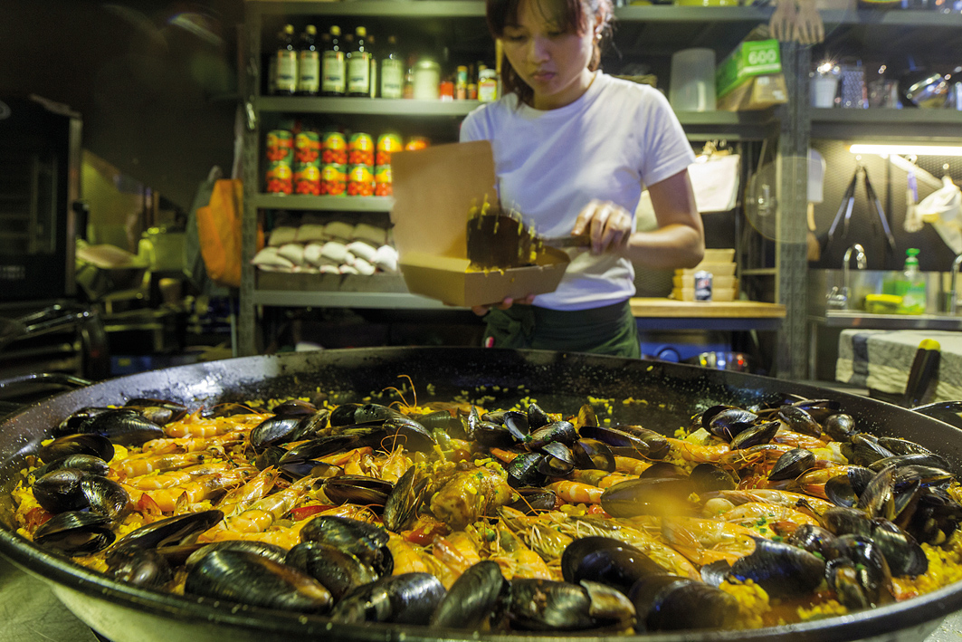 A server scoops up fresh seafood paella.