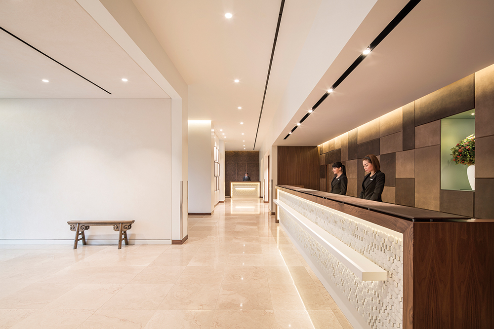 The redesigned reception desk now features a caldding of pale stone and a backdrop of distressed leather panels.