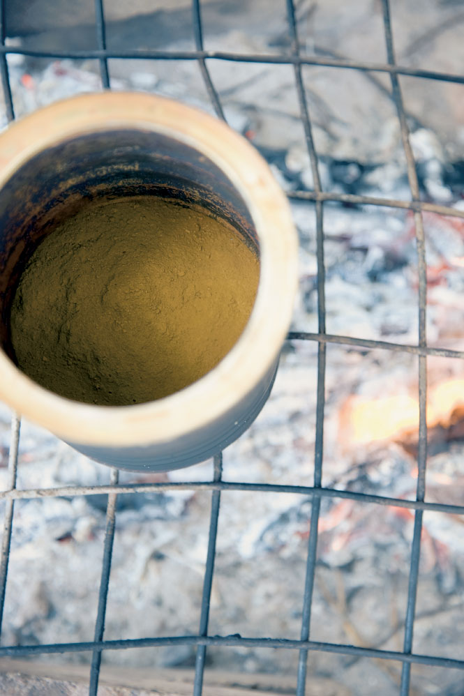 At Tiwi Design on Bathurst Island, ground ocher is heated over a charcoal fire before being made into paint.
