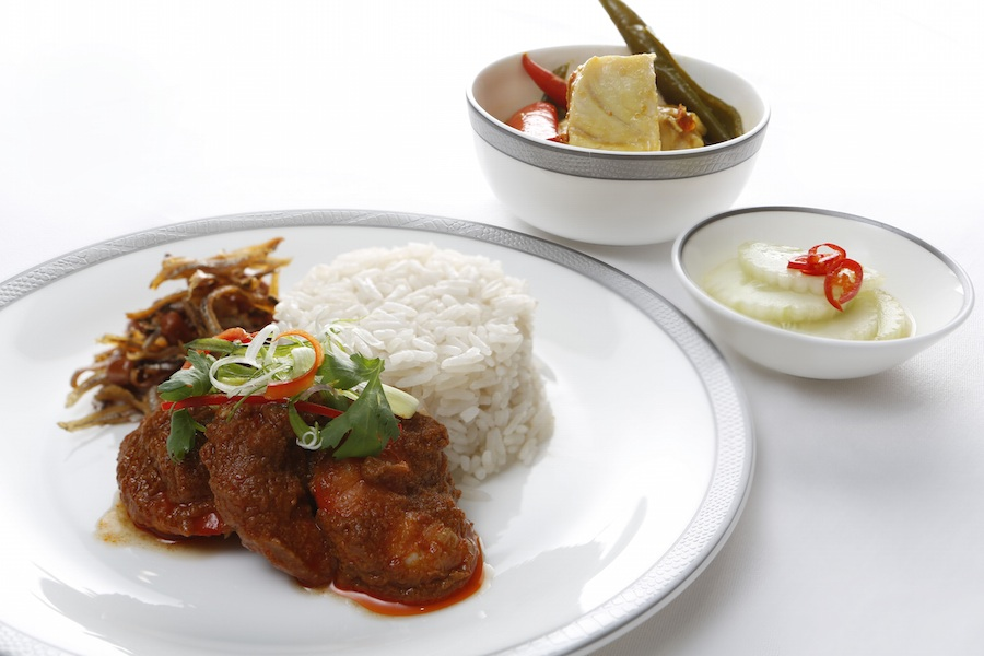 Nyonya nasi lemak, a dish of meat in a spicy sambal sauce served with anchovies, cucumbers, and coconut rice.