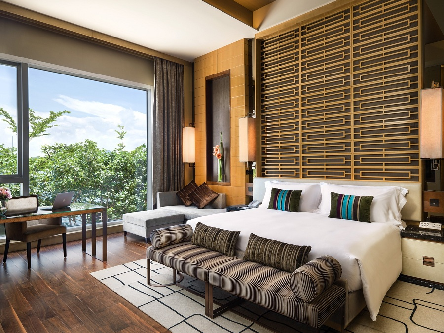A Deluxe Room at the hotel affords views of greenery and a king-size bed.