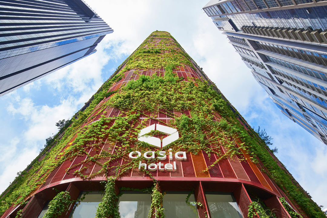 Red aluminum mesh and leafy foliage envelope Oasia Hotel Dowtown's facade.