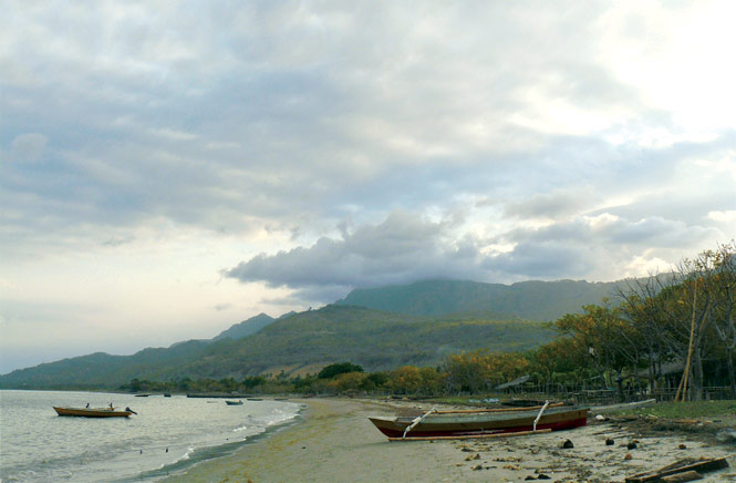 Low clouds shroud a forested ridge overlooking a beach at Beloi, Atauro's near-comatose main port.