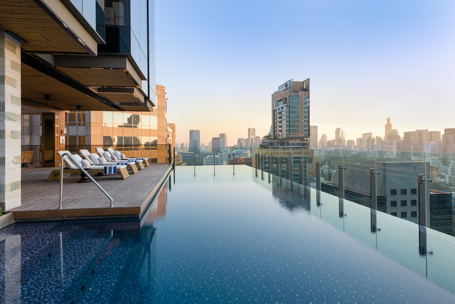 Facilities include a fitness center and outdoor infinity pool overlooking the city's skyline.