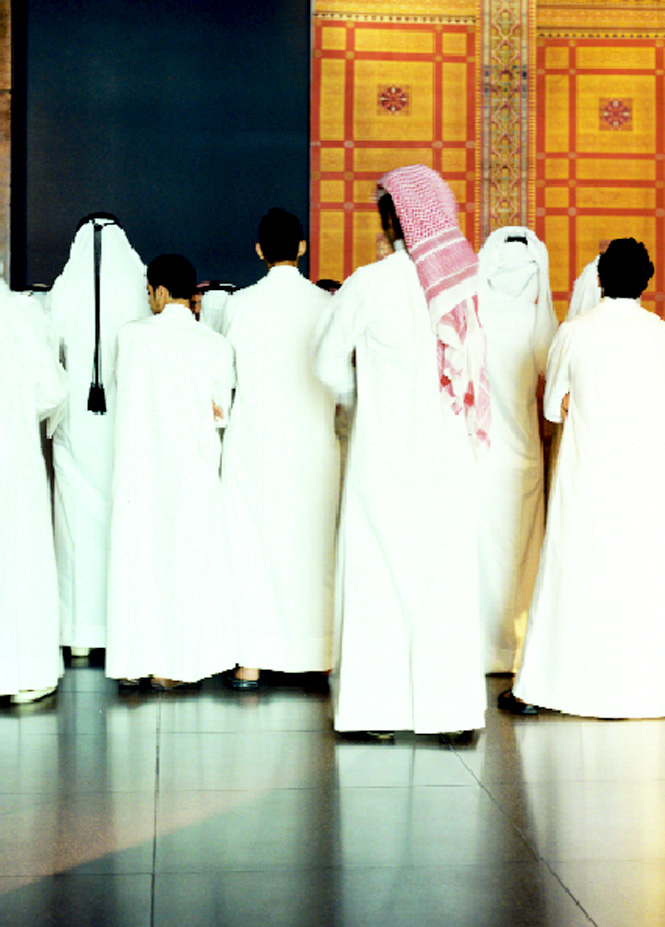 A group of Qatari students in an exhibition hall.