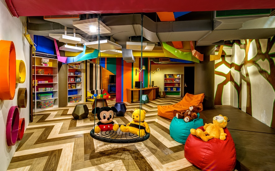 Puzzles, books, video games, and a rope swing fill the colorful space.