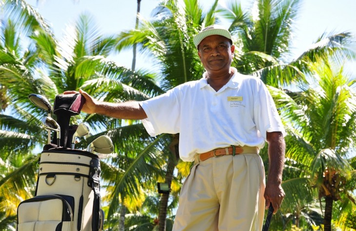 Ramesh pauses with his clubs on the course.