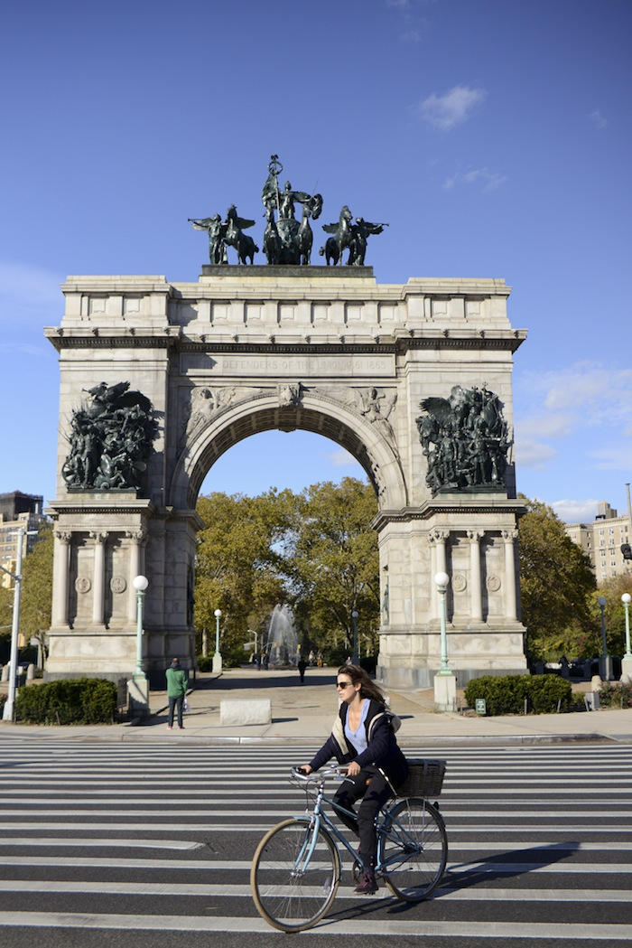 A woman cycles in Grand Army Plaza.