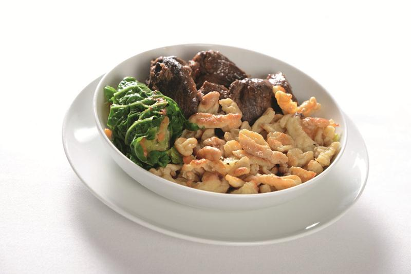 Swiss specialties, such as this venison ragout, spatzle, and savoy cabbage dish, shine on the Swiss business-class menu.