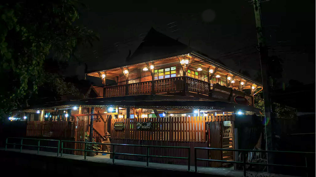 A front look of the wooden Thai-style house.