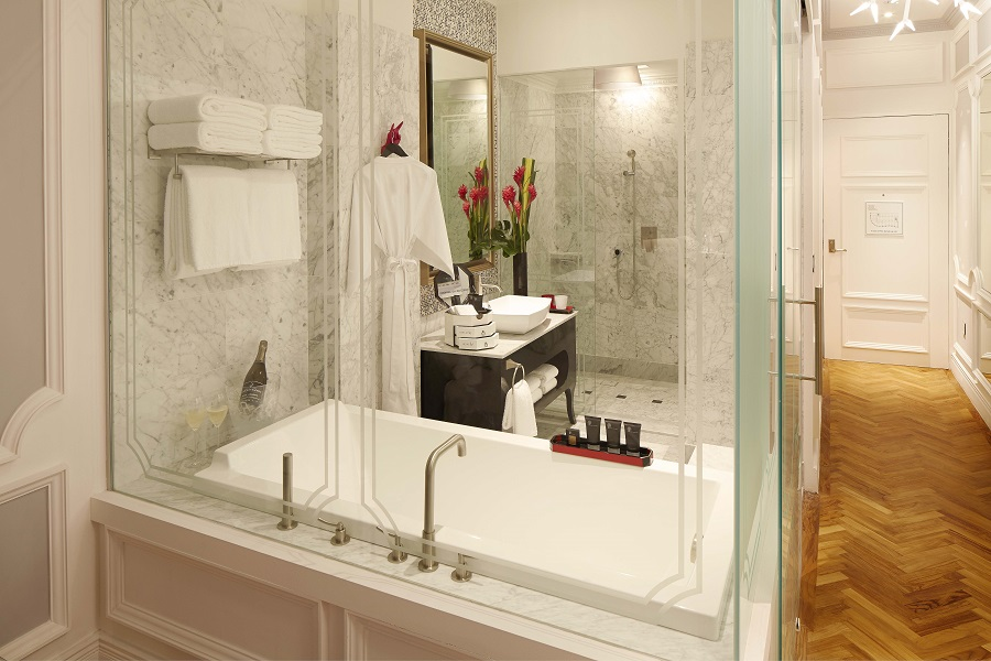 Glassy bathrooms are bedecked with his-and-hers Urban Forest amenities.