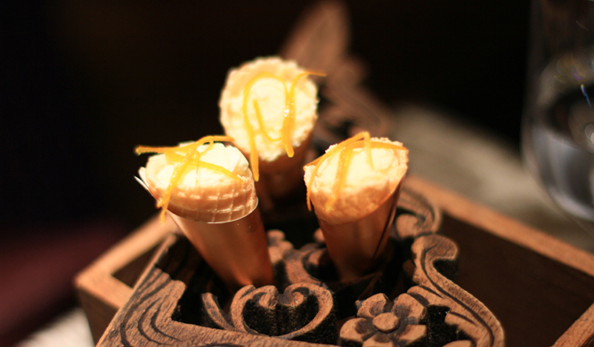 Mignardises — white chocolate mousse in crispy cone with orange peel.