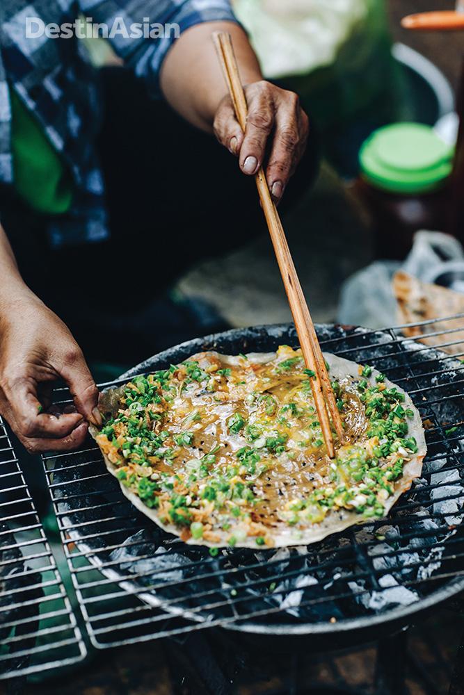 A street vendor preparng banh trang nuong, a quintessential Dalat snack often described as a cross between a pizza and a burrito.
