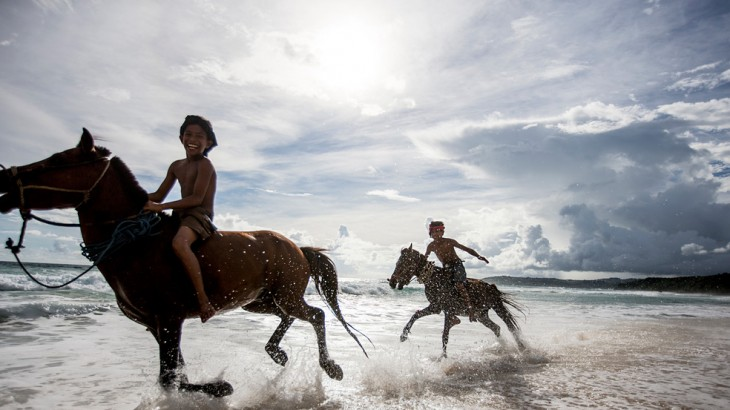 Village boys galloping through the surf.