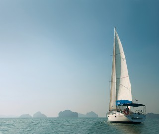 The sloop Papaya sailing into the karst-studded seascape of Phang Nga Bay, most of which is protected as a national marine park.