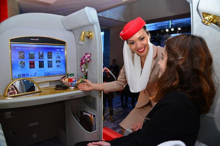 An Emirates flight attendant explaining the entertainment center.
