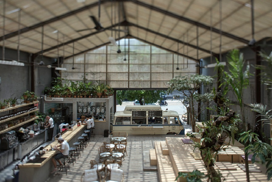 Three Buns feels like an indoor park with street-art-style murals, greenery, and a translucent roof.