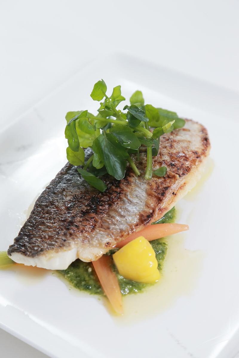 Fillet of sea bass, spring vegetables, and pesto dressing sauce
