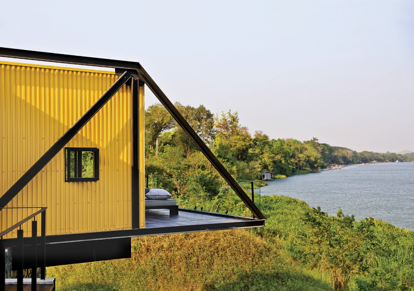 Perched atop the resort's lodge, the cabin's suspended terraces look out toward the Kwai Noi River.