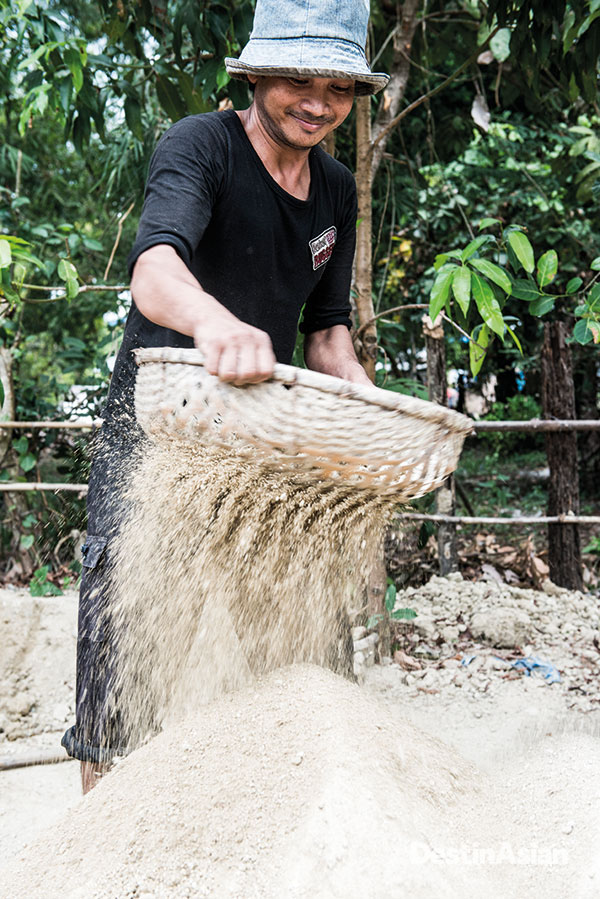 A potter in Andong Russei sifting dry clay powder.