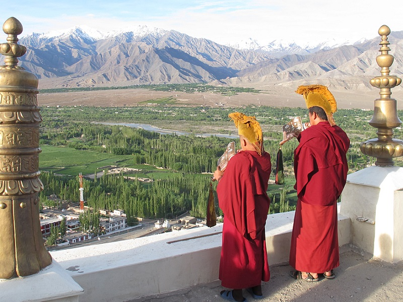 Monks blow conch shells from the monastery's terraces.