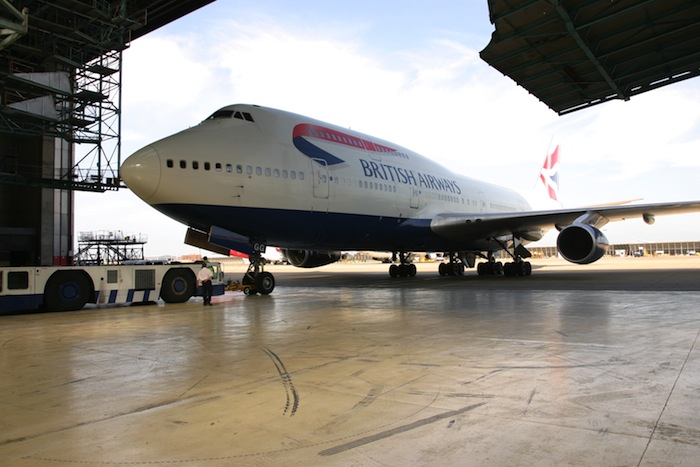 A British Airways Boeing 747 taxis into a aircraft hanger.