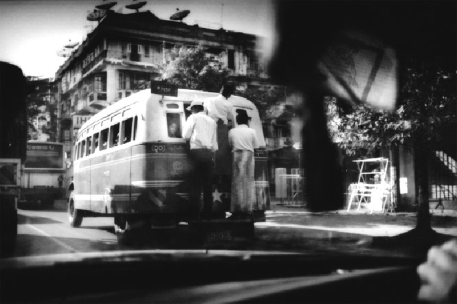 An ancient, overflowing bus typifies public transport in Yangon, the country's largest city and its capital up until 2006, when the junta moved its seat 600 kilometers north to Naypyidaw.