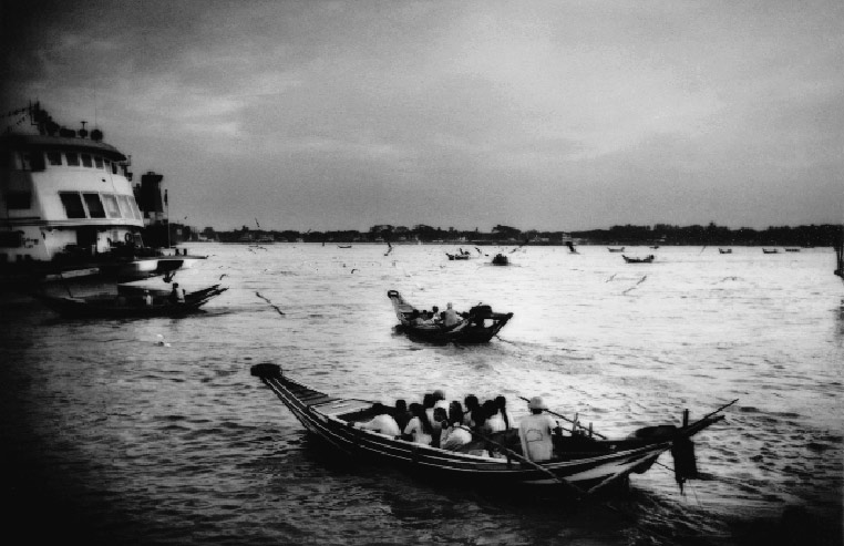 Boats ferrying passengers across the Yangon River, a waterway that was severely battered by the recent cyclone.
